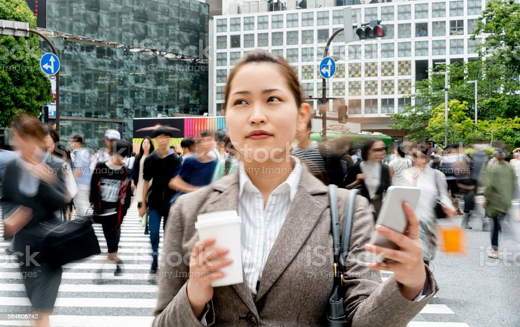 Asian business woman using phone outdoors stock photo