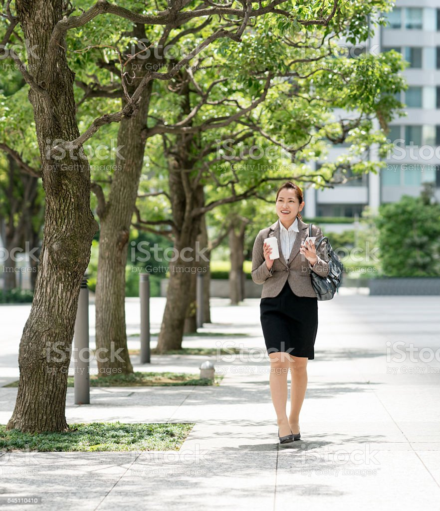 Asian business woman walking outdoors stock photo