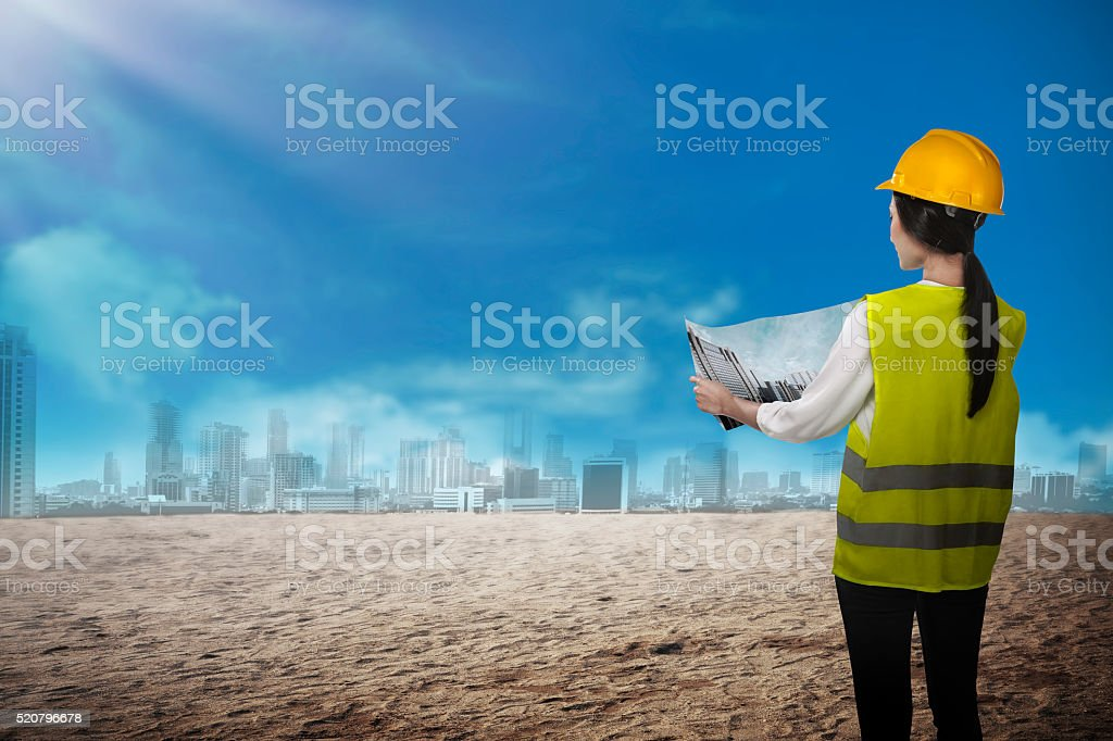 Asian business woman wear yellow helmet looking blueprint to bui stock photo
