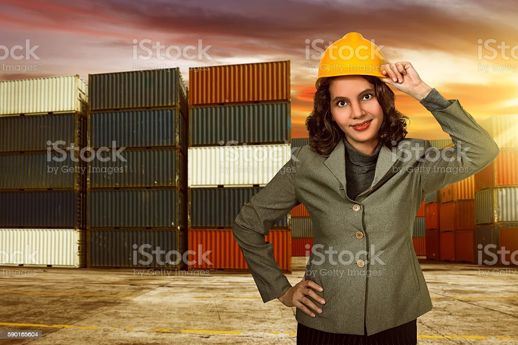 Asian business woman wearing yellow helmet on harbour stock photo