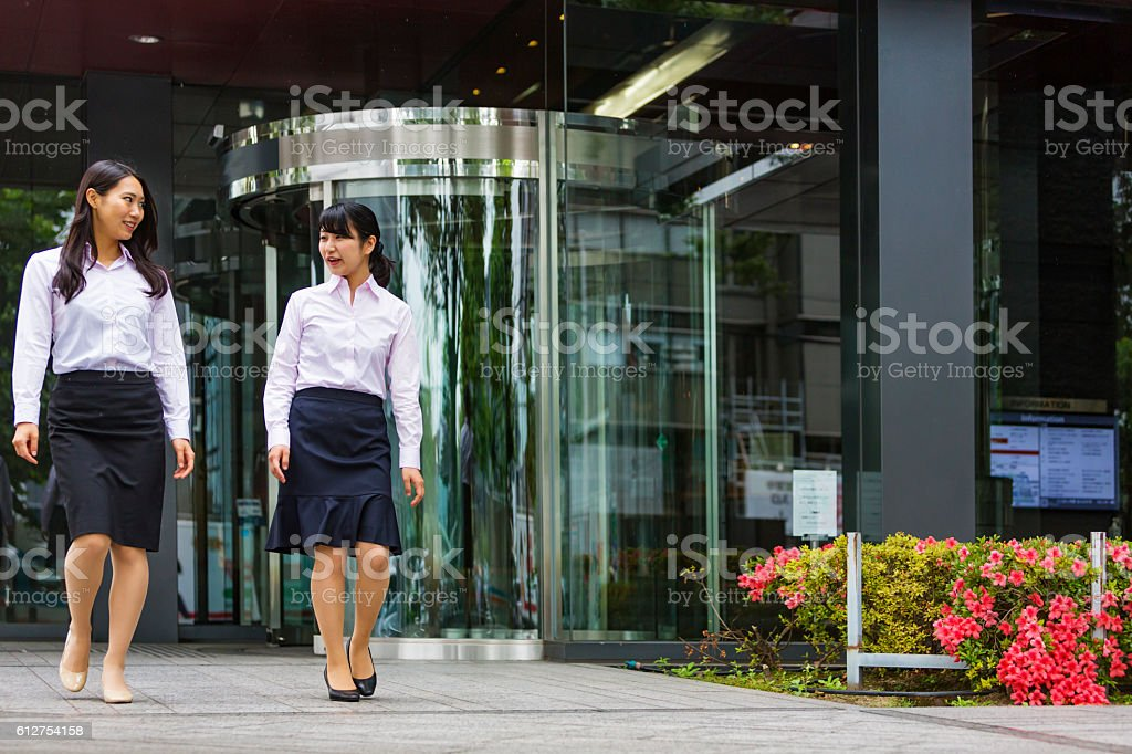 Asian Business Women Walking Outside a Japanese Corporate Office Building stock photo