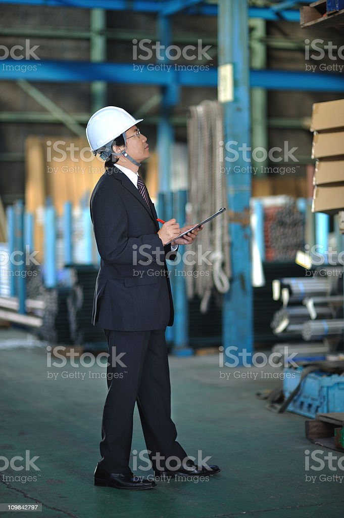 Asian Businessman Checking Inventory in a Warehouse royalty-free stock photo