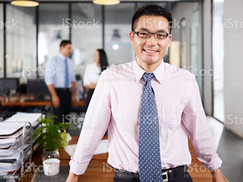 asian businessman standing in office stock photo