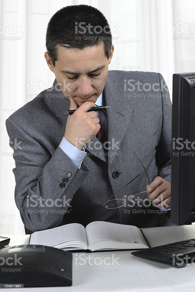 Asian Businessman thinking over his Works in Office royalty-free stock photo