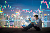Asian Businessman using a laptop and smart phone analysis stock