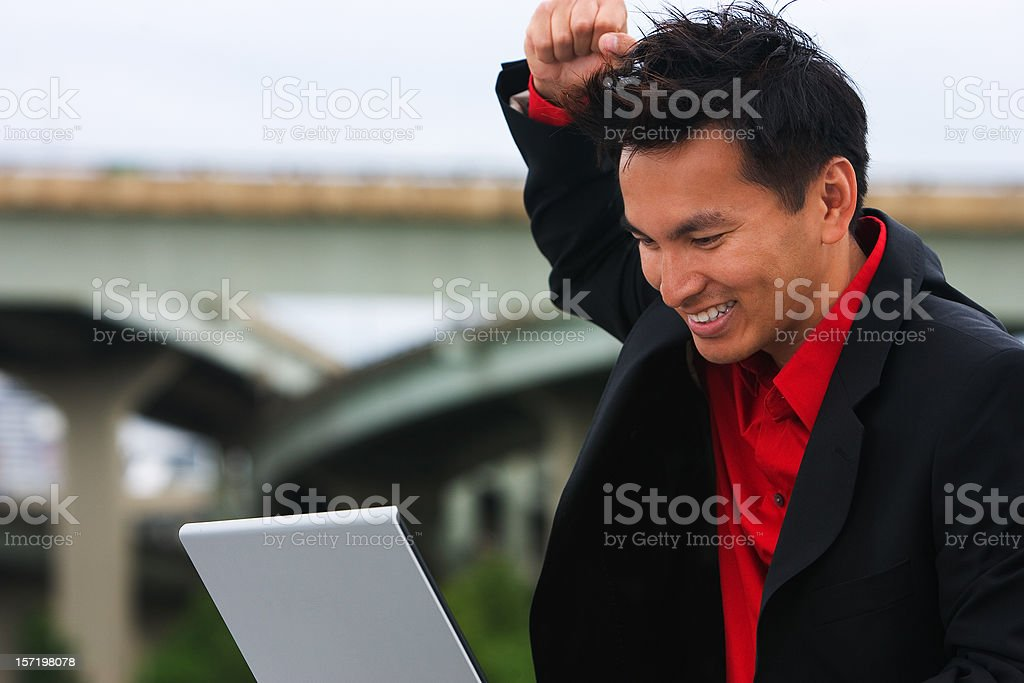 Asian Businessman Using Laptop Outside Gets Good News, Copy Space royalty-free stock photo