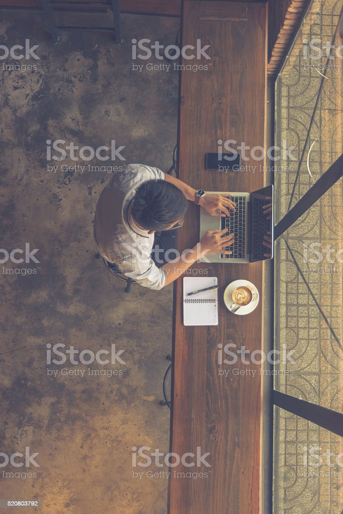 Asian businessman using laptop with smartphone and note beside stock photo