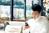 Asian businessman using smartphone during break in cafe.