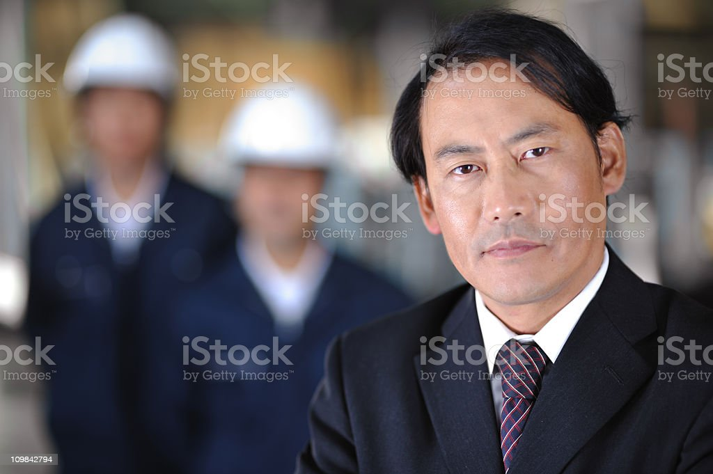 Asian Businessman with Workers in a Warehouse royalty-free stock photo