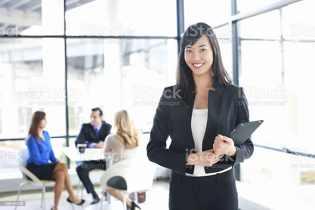 Asian Businesswoman Holding Tablet, Business Team in Background royalty-free stock photo