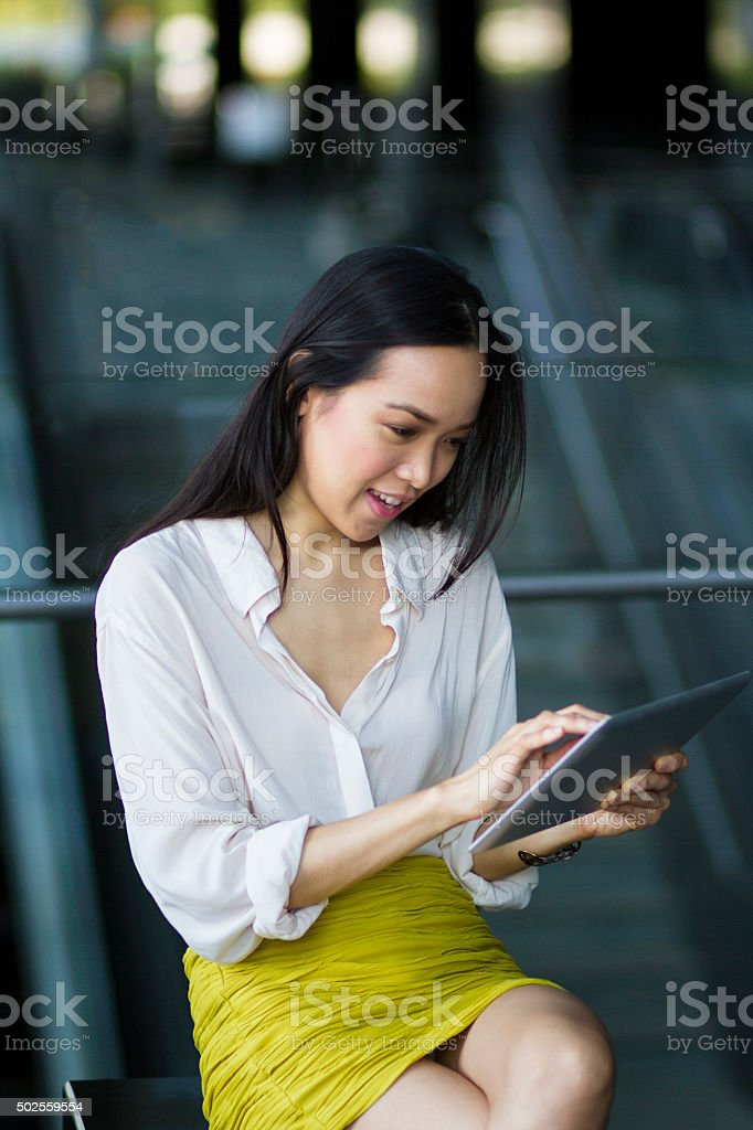 Asian businesswoman using a digital tablet indoors stock photo