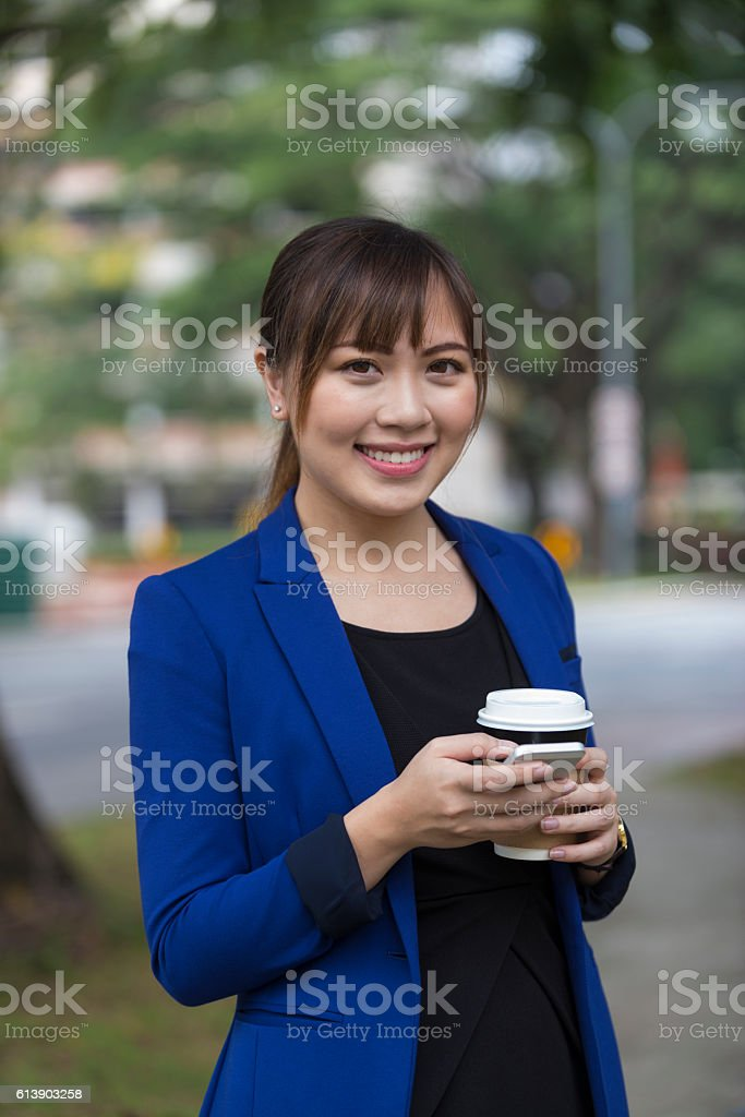 Asian Businesswoman Using Mobile Phone During Coffee Break stock photo