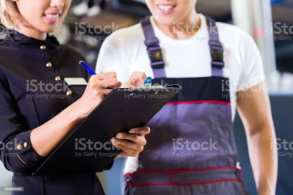 Asian Car mechanic and manager assigning tasks stock photo
