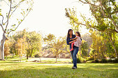 Asian Caucasian woman carrying her young daughter in a park