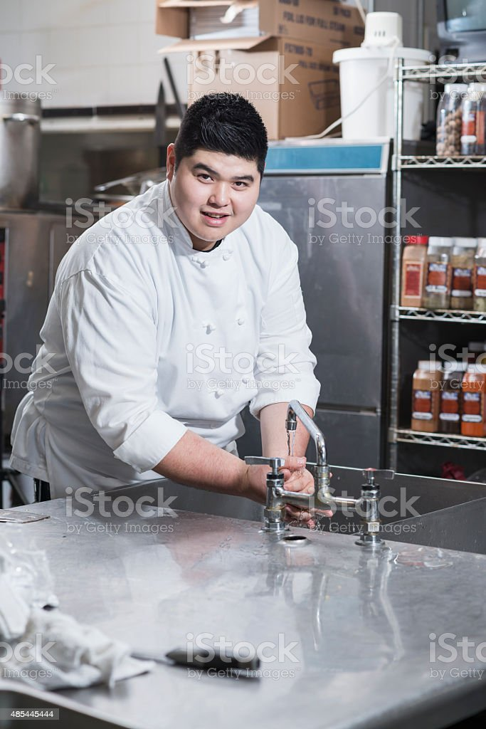 Asian chef washing hands in kitchen sink stock photo