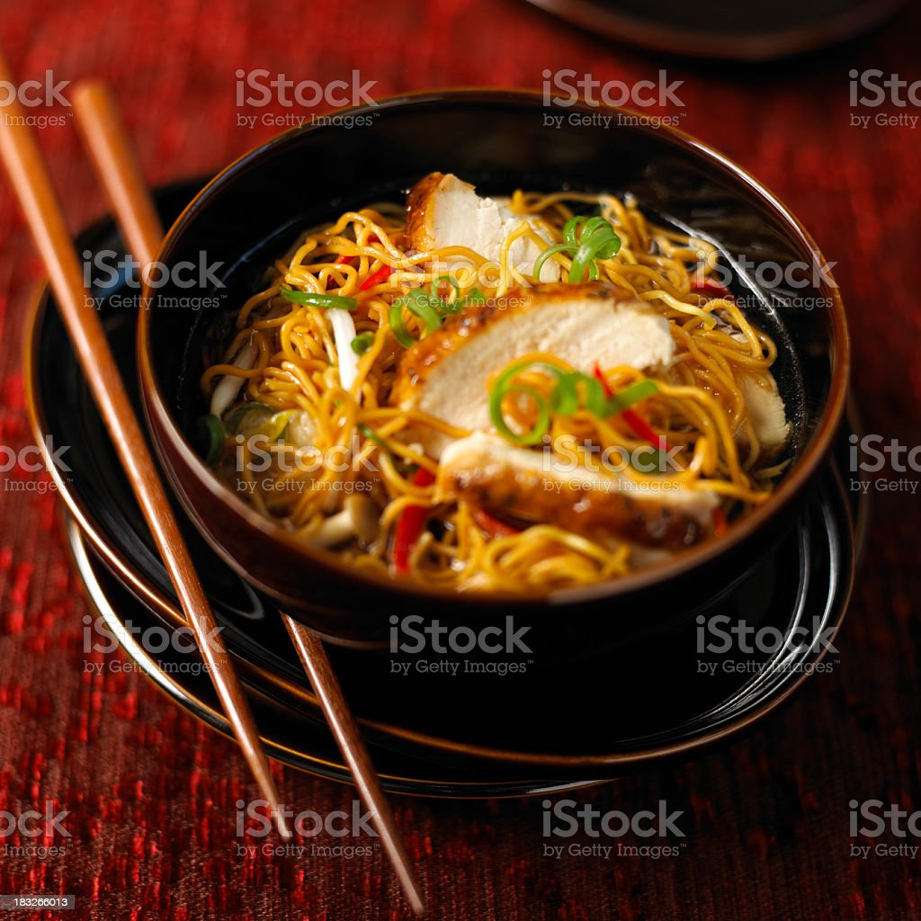 Asian chicken soup with udon noodles eaten with chopsticks stock photo