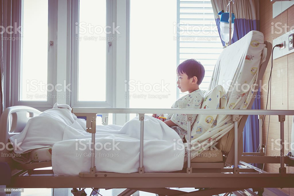 Asian child admitted at hospital room with infusion pump intrave stock photo