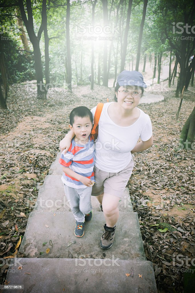 Asian child and mother hiking in the mountain stock photo