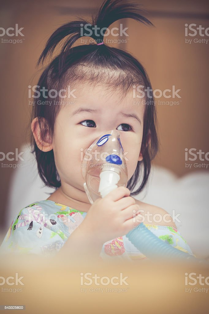 Asian child holds mask vapor inhaler for treatment of asthma. stock photo