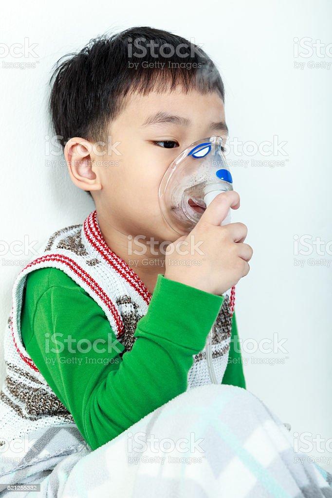 Asian child holds mask vapor inhaler for treatment of asthma. stock photo