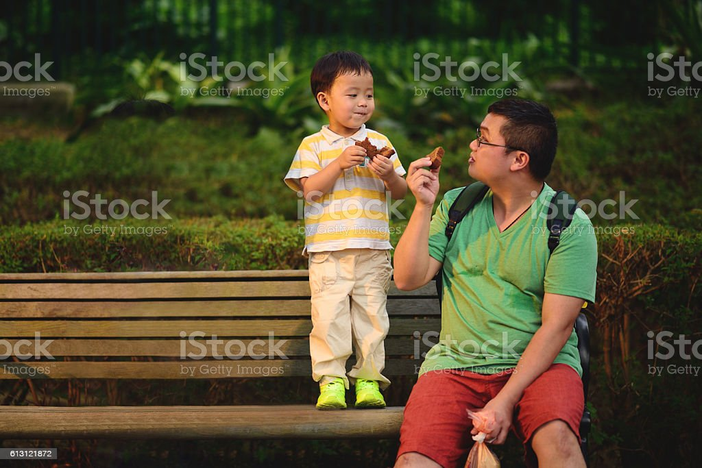 Asian child share food with father stock photo