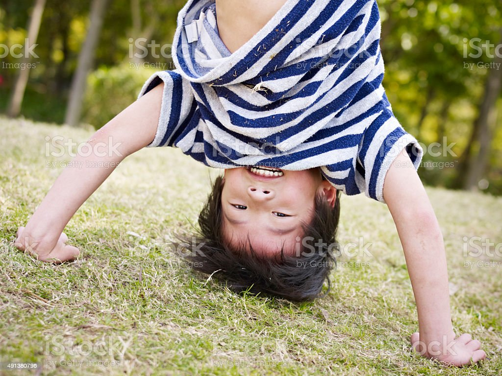 asian child standing on hands outdoors stock photo