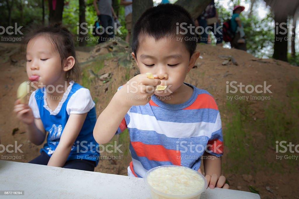 Asian children eat food outdoors stock photo