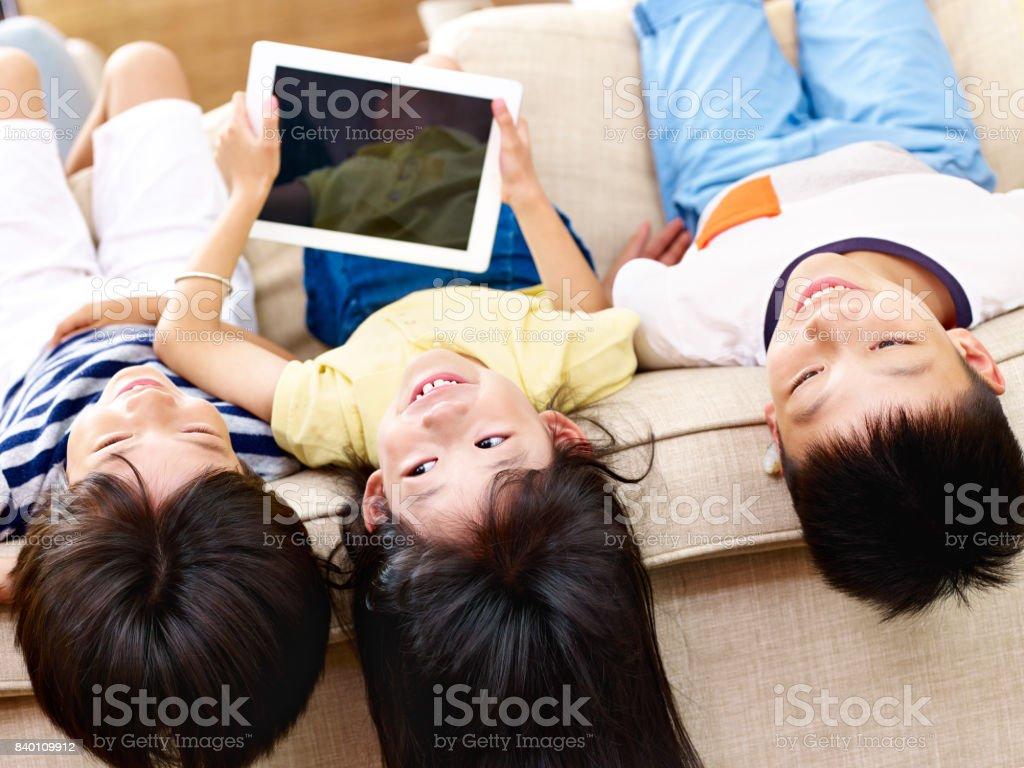 three asian children having fun lying upside down on sofa.