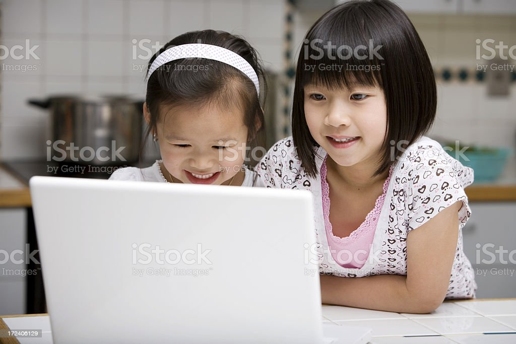 Asian Children Smiling and Using Laptop in Home Kitchen, Copyspace royalty-free stock photo