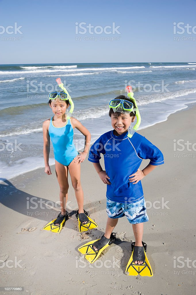 Asian children with masks, snorkels and fins at beach royalty-free stock photo