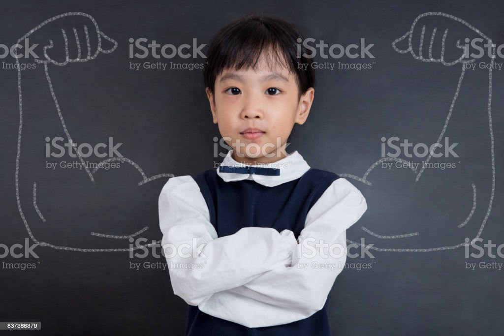 Asian Chinese girl standing against blackboard with sketched strong arms stock photo