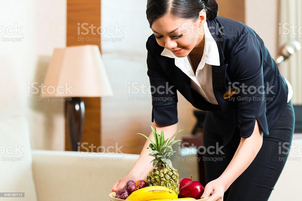 Asian Chinese hotel housekeeper placing fruit stock photo