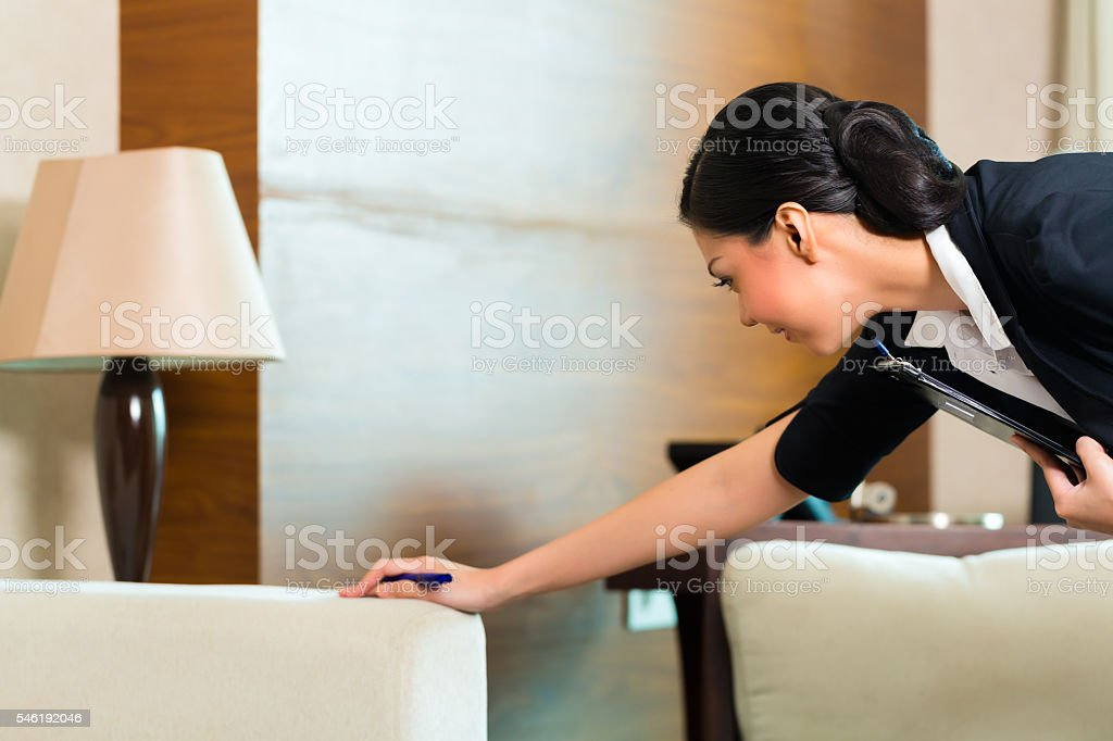 Asian Chinese housekeeper controlling hotel room stock photo