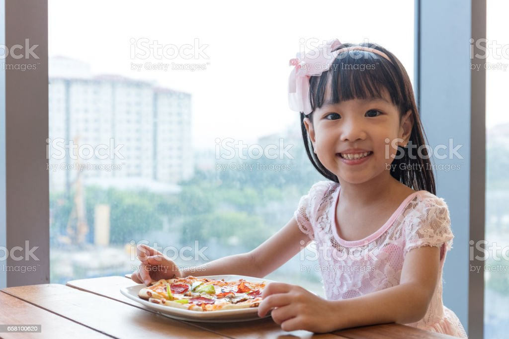 Asian Chinese little girl eating pizza pepperoni stock photo