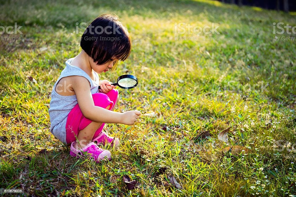 Asian Chinese Little Girl Exploring With Magnifying Glass stock photo