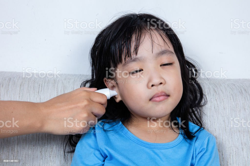 Asian Chinese little girl getting ear measurement for fever temperature stock photo