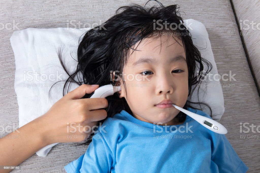 Asian Chinese little girl getting measurement for fever temperature stock photo