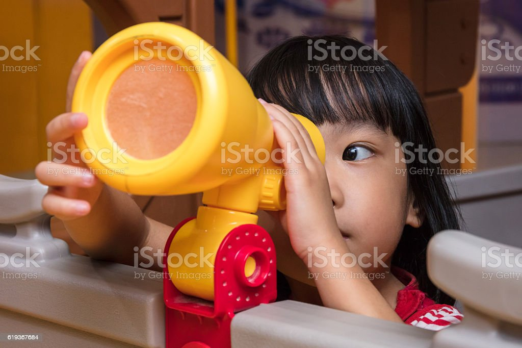 Asian Chinese little girl looking through a toy telescope stock photo