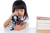 Asian Chinese little girl looking through microscope