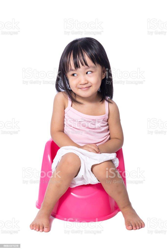 Asian chinese little girl sitting on chamberpot stock photo