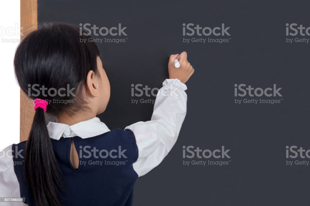 Asian Chinese little girl writing on blackboard stock photo