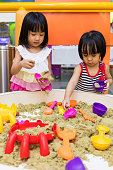 Asian Chinese Little Sister Playing Kinetic Sand Indoor