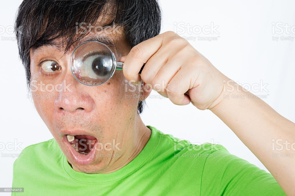 Asian Chinese Man Looking through a Magnifying Glass stock photo