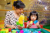 Asian Chinese mother and daughter playing blocks at playground