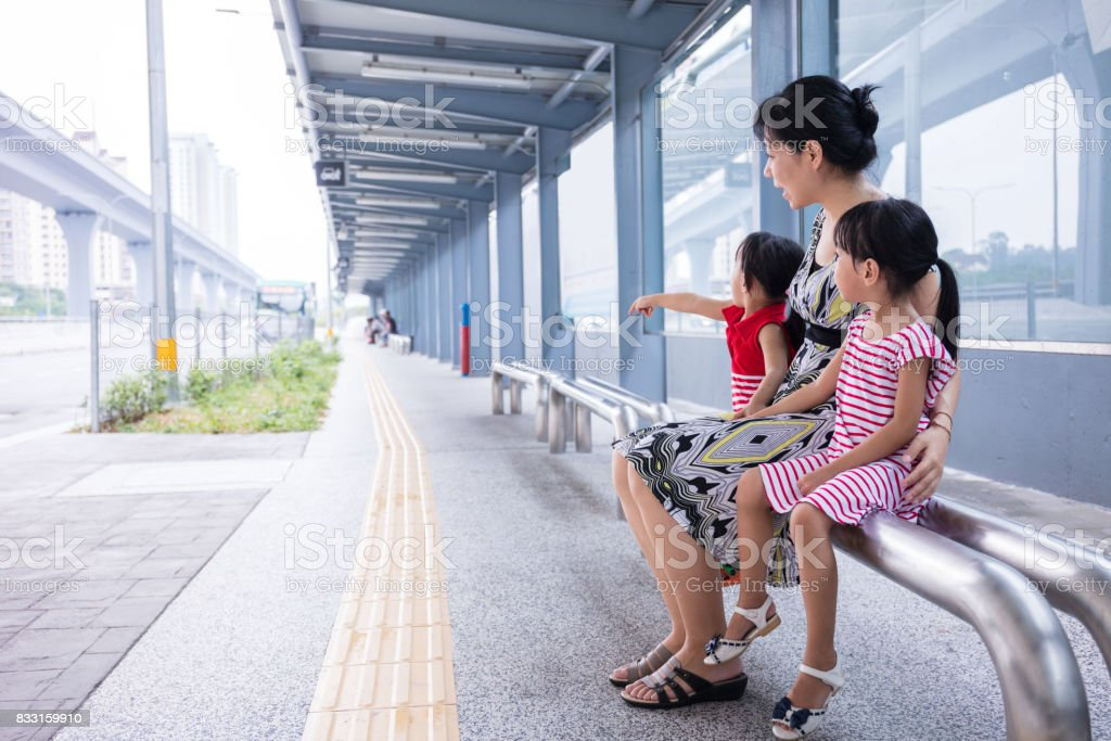 Asian Chinese mother and daughters waiting for a bus stock photo