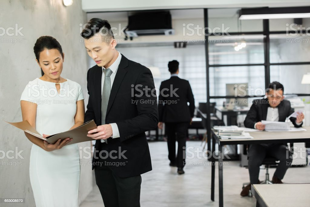 Asian colleagues discussing work in the office stock photo