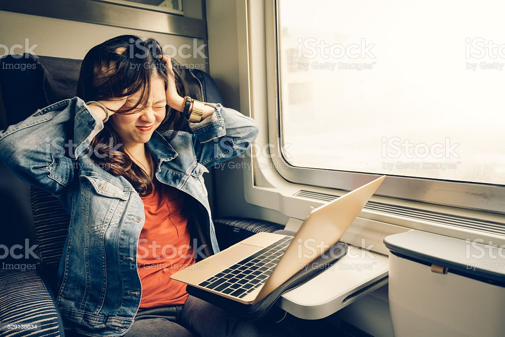 Asian college girl frustrated with laptop on the train stock photo