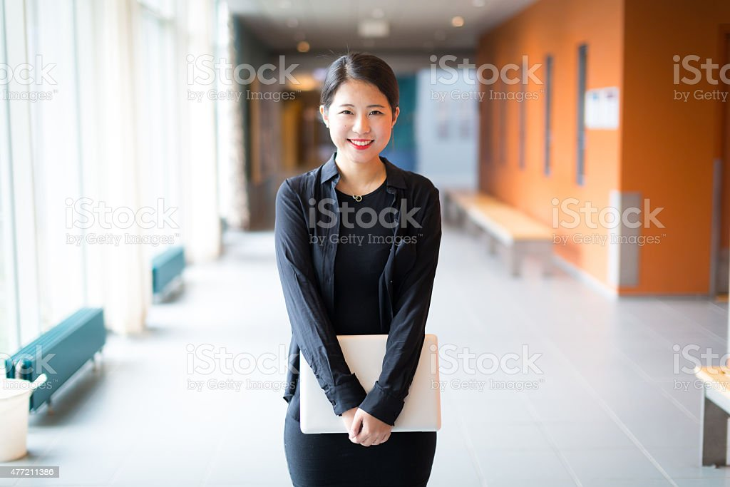 Asian college student standing with a laptop stock photo