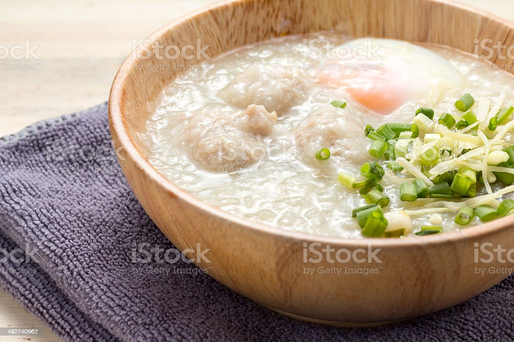 Asian congee with minced pork and egg in white bowl. stock photo