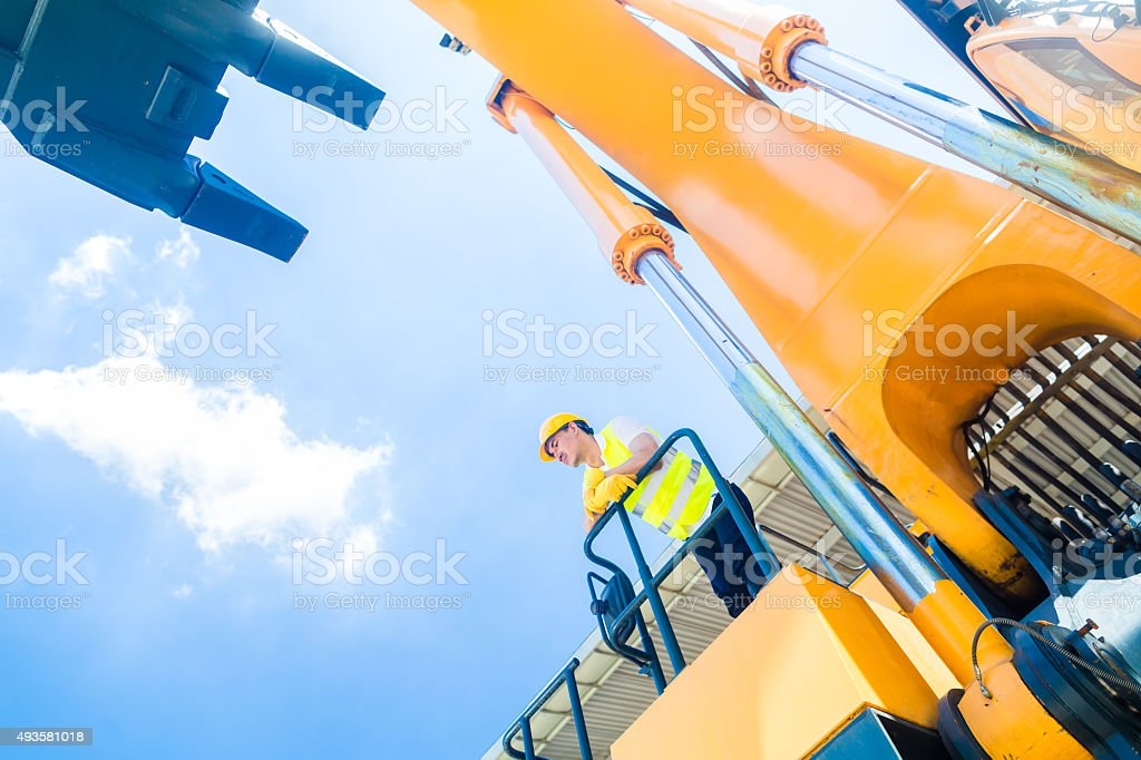 Asian construction worker on shovel excavator stock photo